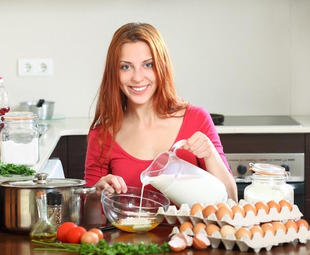 Mulher cozinhando ovos mexidos na cozinha doméstica
