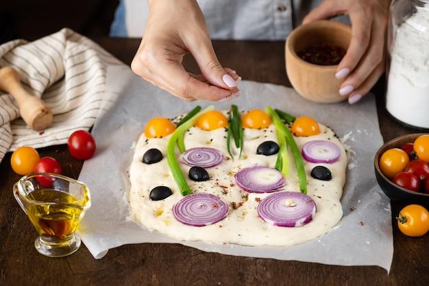 Mulher cozinhando pão focaccia italiana com vegetais e ervas focaccia de jardim