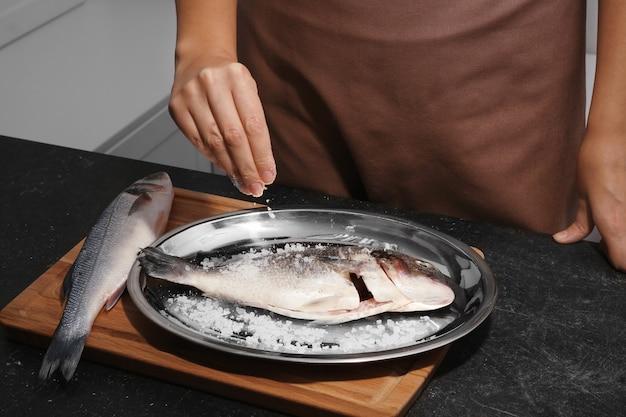 Mulher cozinhando peixe cru na cozinha