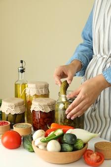 Mulher cozinhando pepinos em conserva e vegetais diferentes