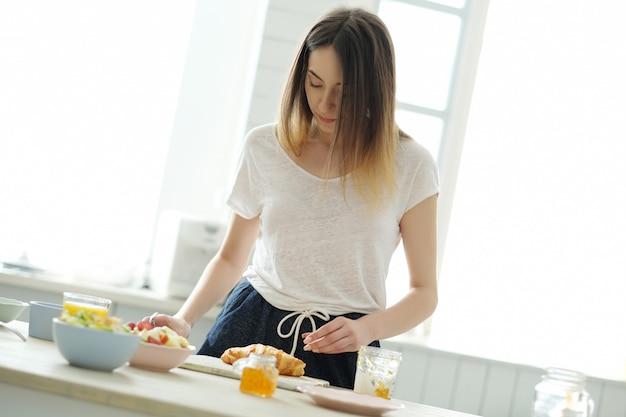 Mulher cozinhando, preparando o café da manhã