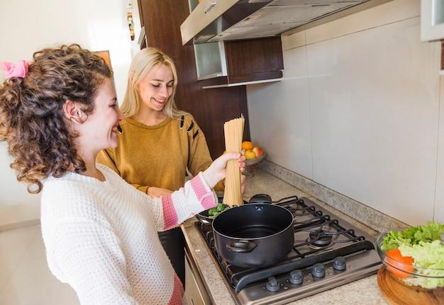 Mulher, cozinhar, espaguete, com, dela, amigo feminino, em, cozinha