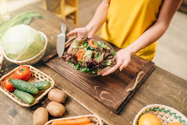 Mulher cozinhar salada na cozinha, preparação de alimentos orgânicos saudáveis. dieta vegetariana, vegetais frescos e frutas na mesa de madeira