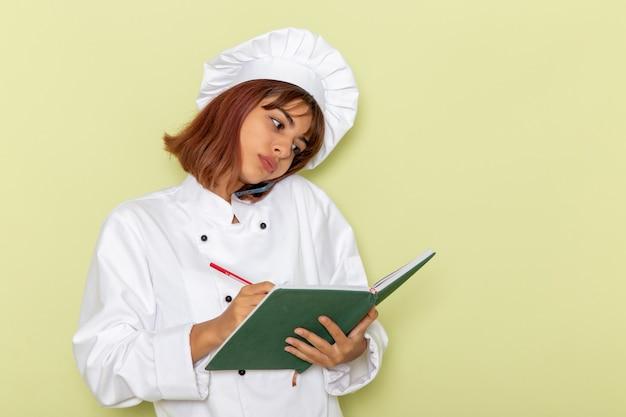 Mulher cozinheira de terno branco falando ao telefone e fazendo anotações em uma superfície verde.