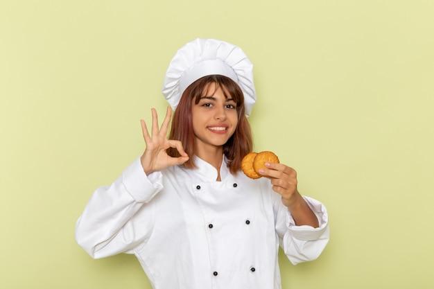 Mulher cozinheira de terno branco segurando biscoitos açucarados na mesa verde