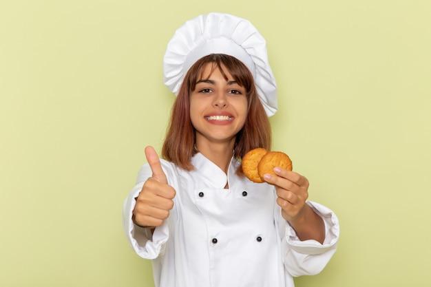 Mulher cozinheira de terno branco segurando biscoitos de açúcar sobre uma superfície verde