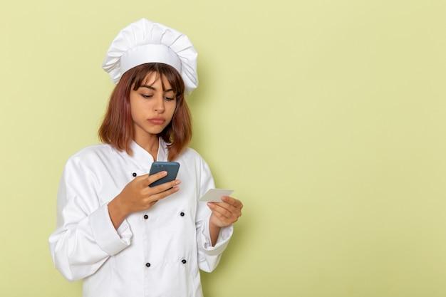 Mulher cozinheira de terno branco segurando o cartão e o smartphone na mesa verde.