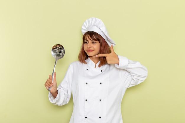 Mulher cozinheira de terno branco segurando uma colher grande de prata na superfície verde-clara.