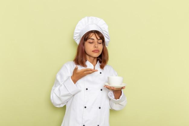 Mulher cozinheira de terno branco segurando uma xícara de chá em uma mesa verde