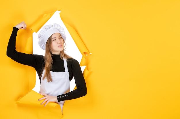 Mulher cozinheira flexionando em amarelo emoção cor papel trabalho cozinha sol comida foto vista frontal