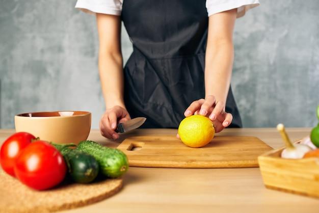 Mulher cozinheira na cozinha cortando dieta de salada de legumes