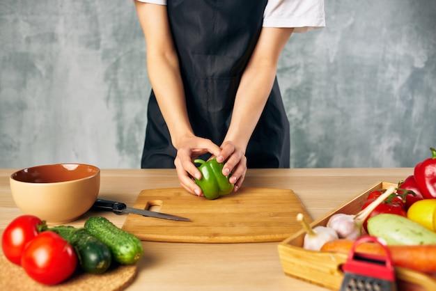 Mulher cozinheira na cozinha cortando legumes