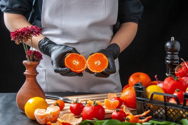 Mulher cozinheira segurando metade das fatias de tangerina no escuro cozinhando salada saúde refeição vegetal comida fruta trabalho dieta