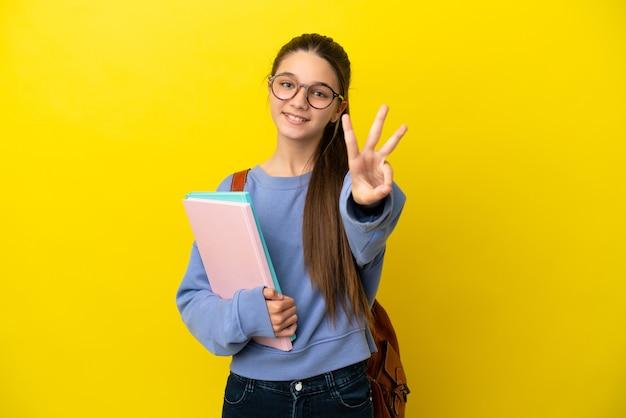 Mulher criança estudante sobre fundo amarelo isolado feliz e contando três com os dedos