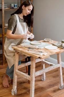 Mulher criativa fazendo uma panela de barro em sua oficina