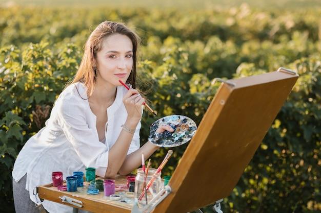 Mulher criativa na pintura da natureza