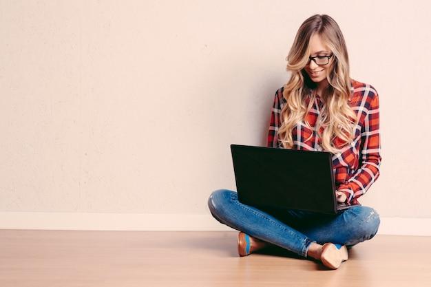 Mulher criativa nova que senta-se no assoalho com portátil.