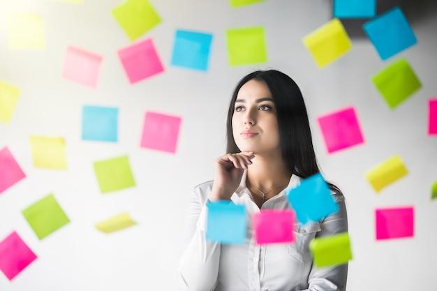 Mulher criativa pensando usar notas para compartilhar a ideia. escritório comercial