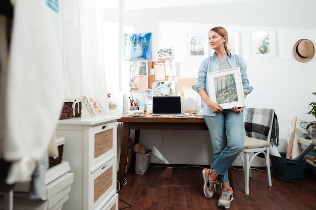 Mulher criativa segurando obras de arte