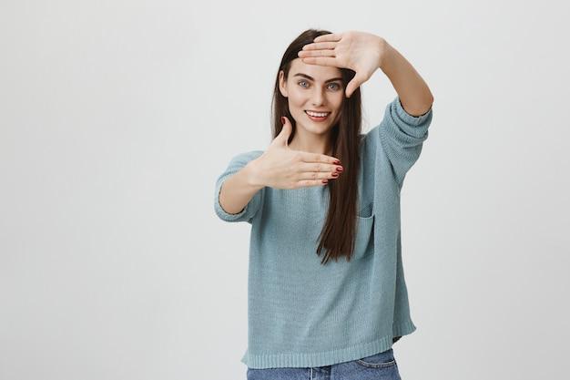 Mulher criativa sorridente fazendo quadro mãos, obtendo inspiração