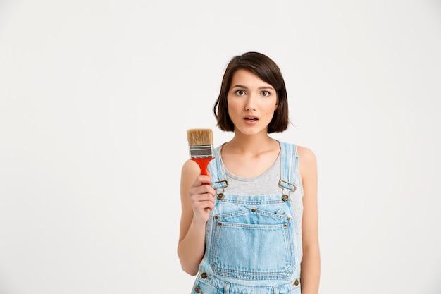 Mulher criativa surpresa com pincel de pintura