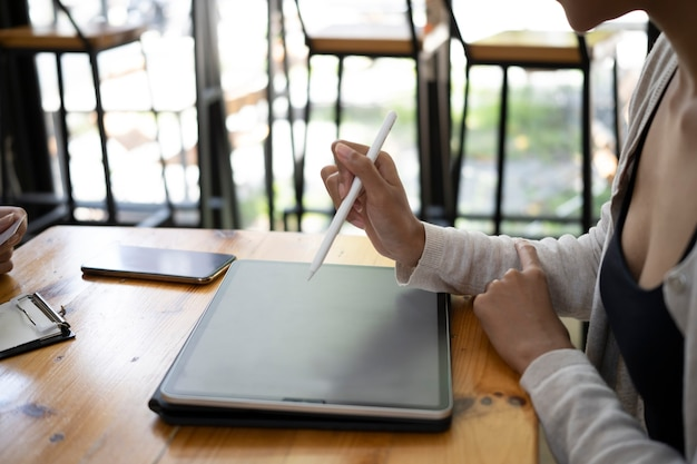 Mulher criativa tiro recortada segurando a caneta stylus e trabalhando com tablet digital.