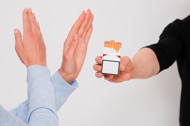 Mulher, cruzado, mãos, recusar, um, cigarro, oferta, por, dela, amigo masculino