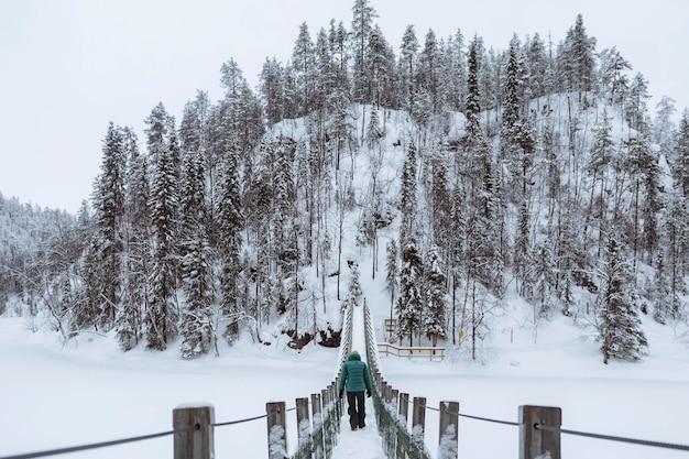 Mulher cruzando uma ponte suspensa em um parque nacional oulanka coberto de neve, finlândia