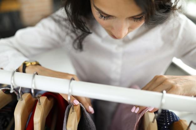 Mulher cuidadosamente escolhe roupas no cabide closeup