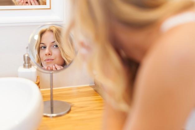 Mulher cuidando da pele do rosto em frente a um pequeno espelho