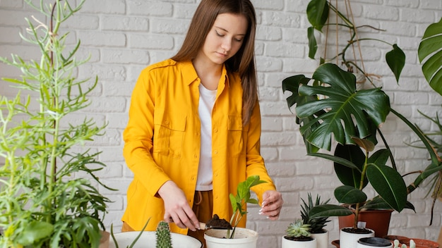 Mulher cuidando das plantas no jardim de sua casa