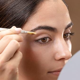 Mulher cuidando das sobrancelhas