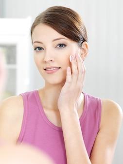 Mulher cuidando de sua linda pele no rosto em pé perto de um espelho no banheiro