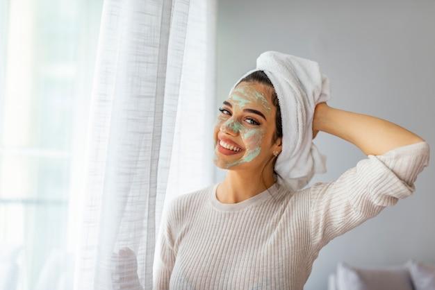 Mulher cuidando de sua pele facial. mulher bonita, aplicar a máscara para o rosto dela. tratamentos de beleza.