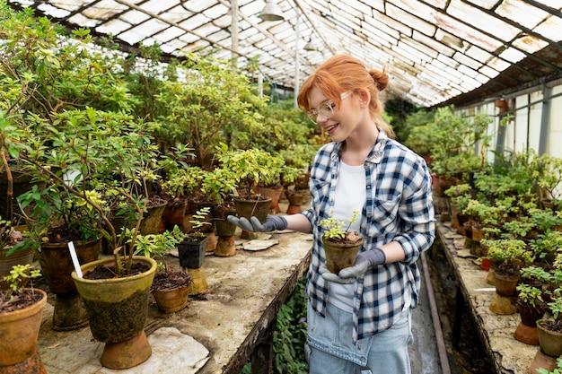 Mulher cuidando de suas plantas em uma estufa