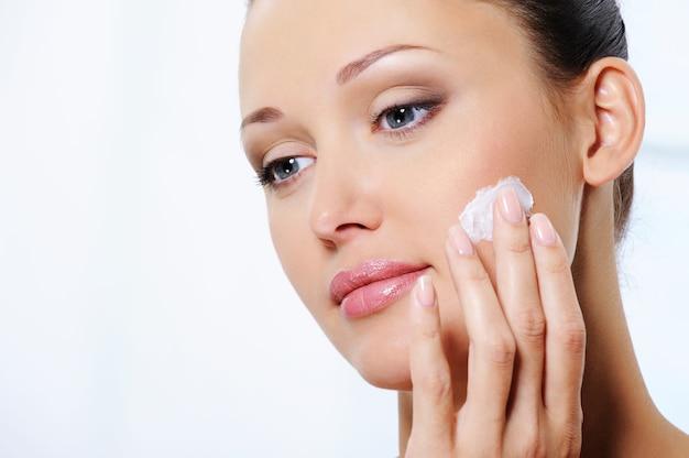 Mulher cuidando do rosto com creme hidratante