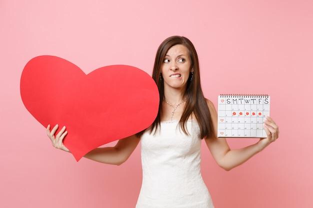 Mulher culpada preocupada em um vestido branco segura um calendário de períodos femininos com coração vermelho em branco para verificar os dias de menstruação
