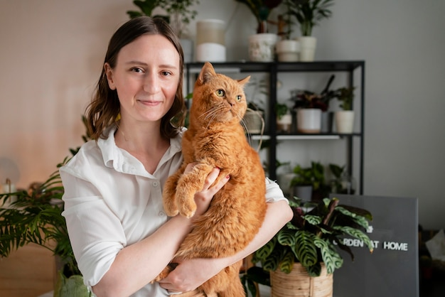 Mulher cultivando plantas em casa segurando um gato