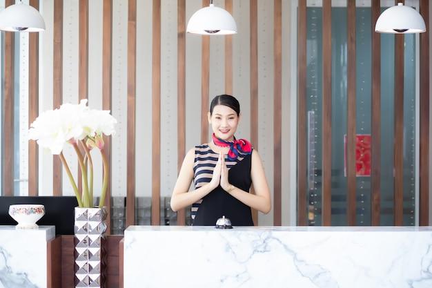 Mulher cumprimenta os clientes no balcão do saguão do hotel.