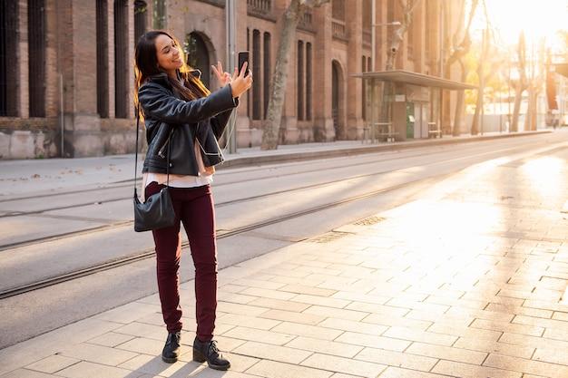 Mulher cumprimentando fazendo uma videochamada na rua