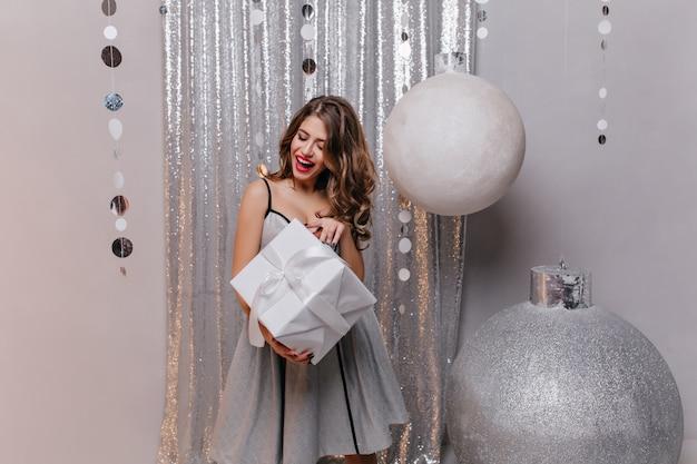 Mulher curiosa de cabelos castanhos em vestido de festa segurando uma caixa de presente. menina despreocupada sorridente com o presente em pé perto de brinquedos de natal grandes.