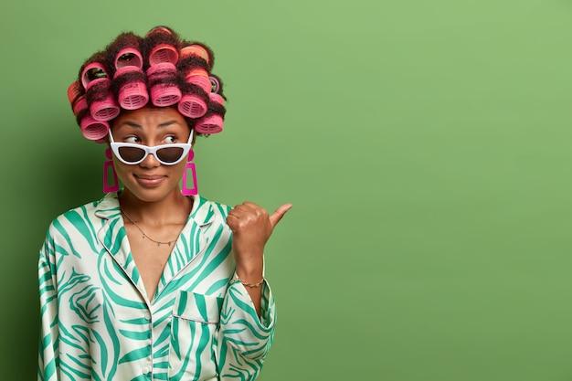 Mulher curiosa de pele escura, usa bobes de cabelo, óculos escuros da moda e roupão, se prepara para um encontro formal com os colegas, quer estar fabulosa, aponta o polegar à parte.