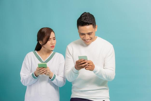 Mulher curiosa espiando e espiando o smartphone do namorado dele enquanto