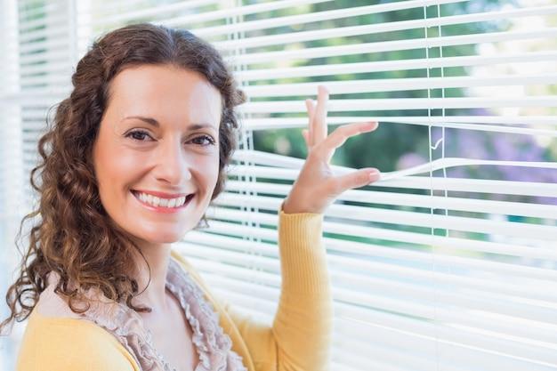 Mulher curiosa olhando através das cortinas
