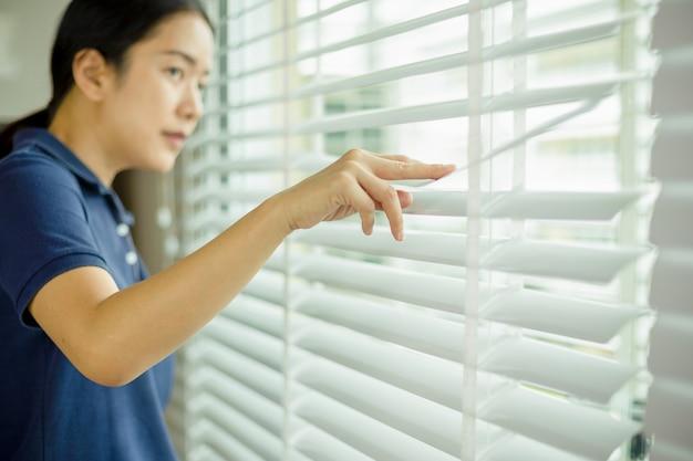 Mulher curiosa que olha através da janela cega.