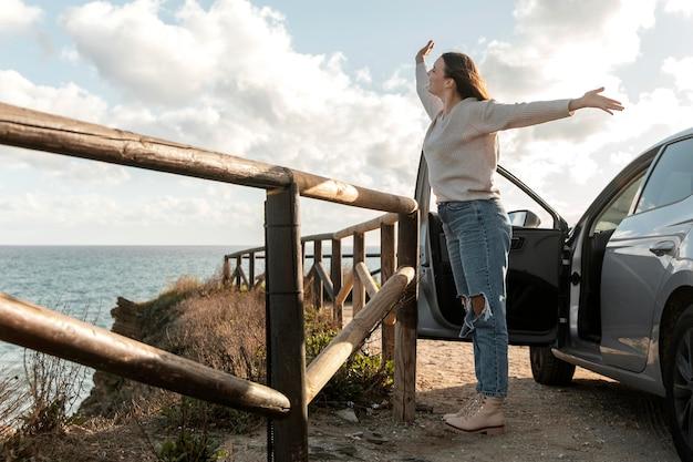 Mulher curtindo a brisa da praia ao lado do carro