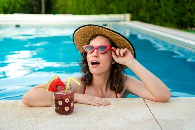 Mulher curtindo o sol na piscina com óculos de sol vermelhos, um chapéu e uma bebida