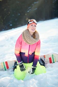 Mulher curtindo snowboard na colina