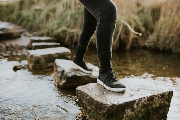 Mulher curtindo uma aventura ao ar livre cruzando o riacho