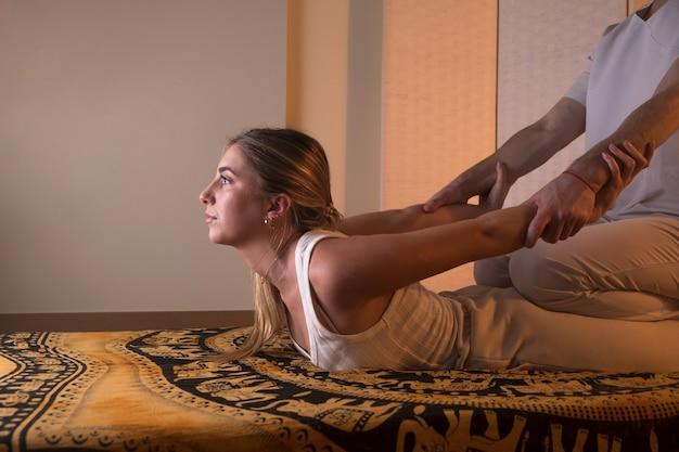 Mulher curtindo uma massagem tailandesa à luz de velas